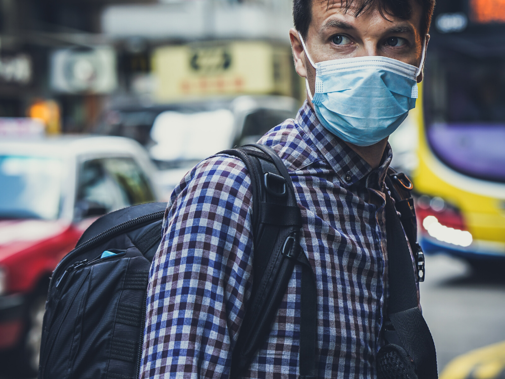 In an article discussing the dangers of stigma and prejudice during a viral pandemic, a man is pictured on the streets with a face mask to prevent a higher chance of catching an illness.
