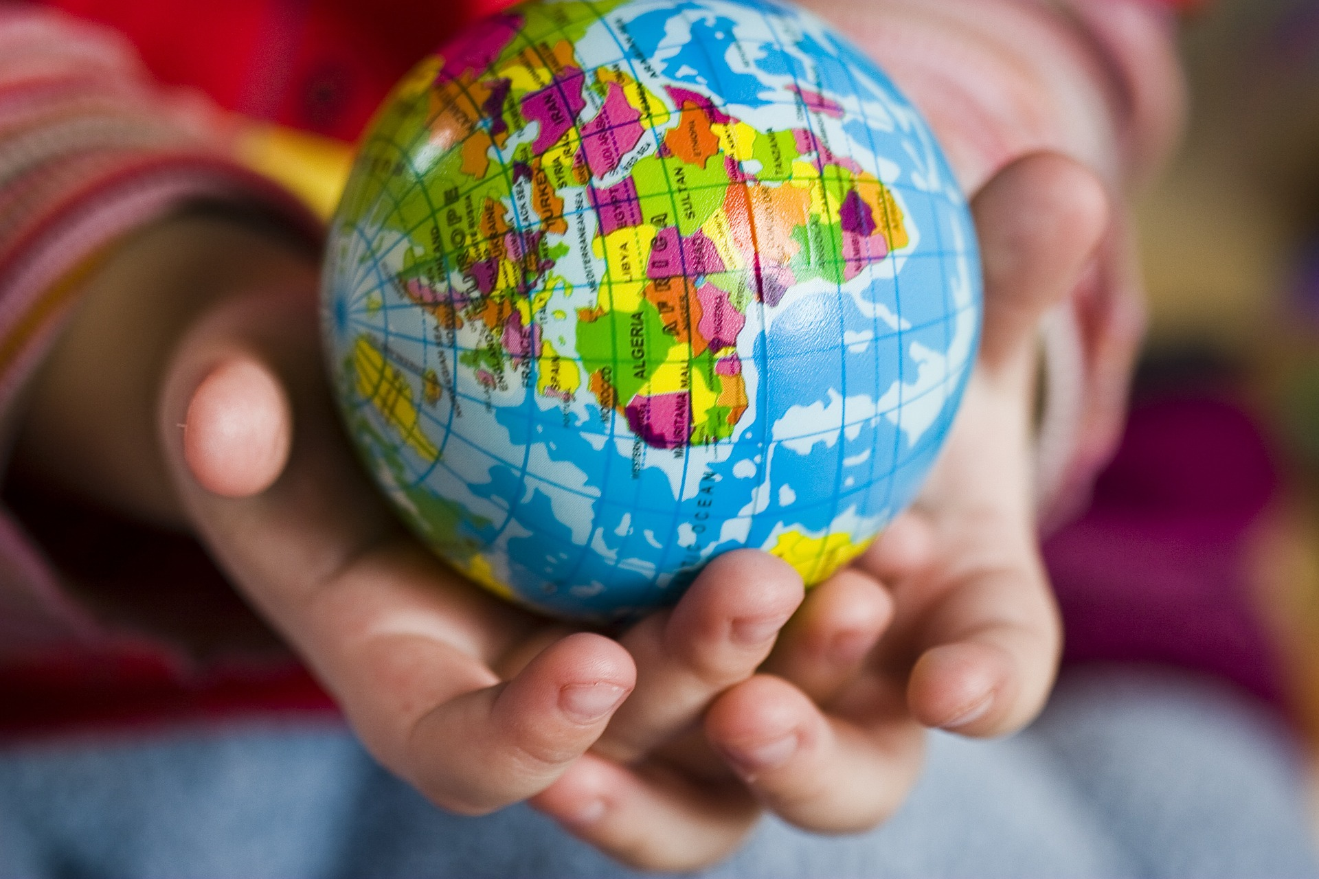 A hand holding a small globe in an article about third culture kids