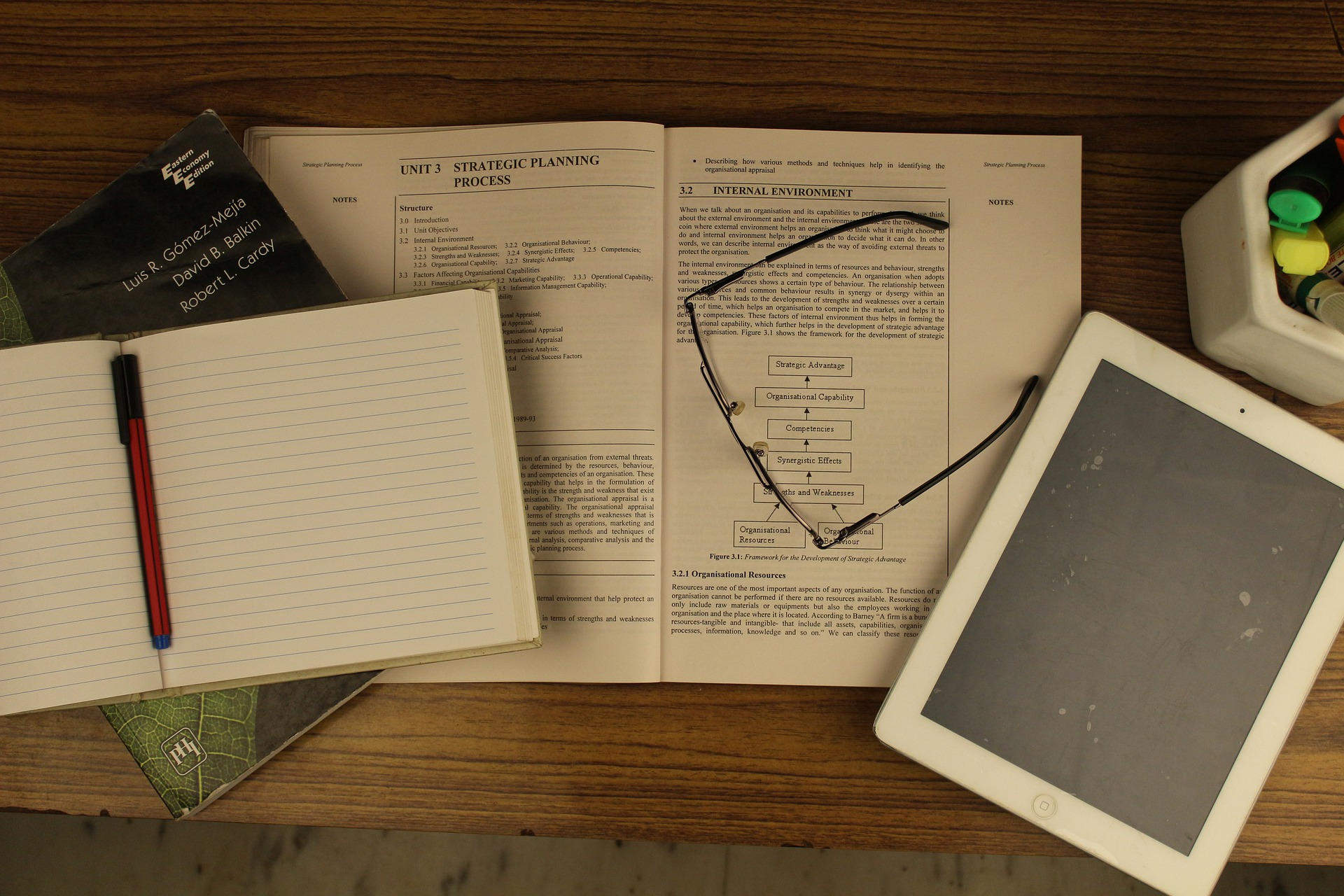 iPad next to notebook and open textbook in article about taking digital notes.