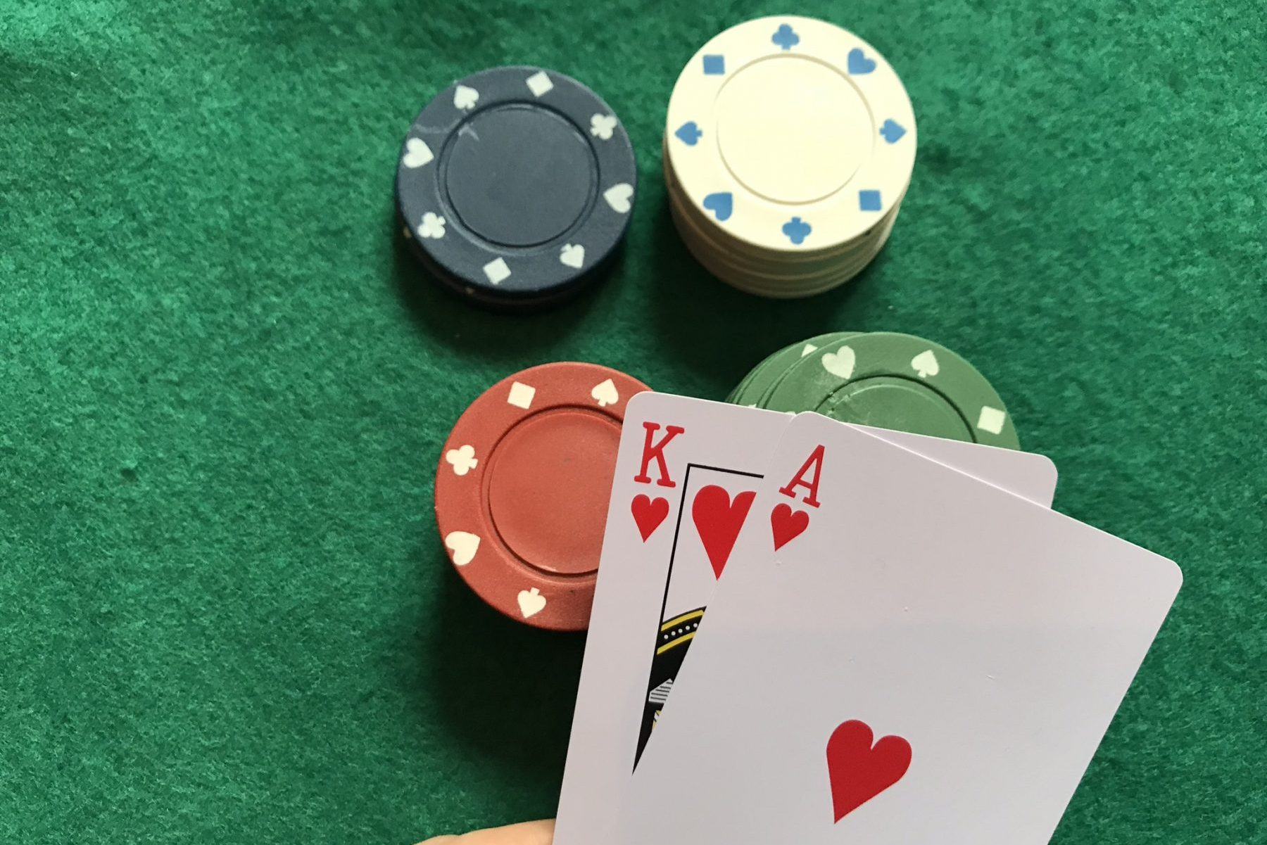 In an article about card counting, a person holding a a King and an Ace over some casino chips