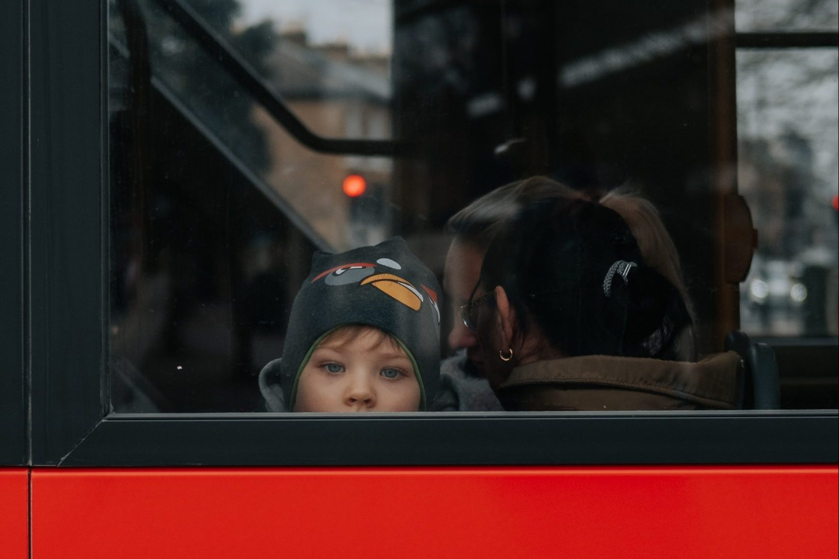 In an article about gender, a photo a child looking out the back window of a bus