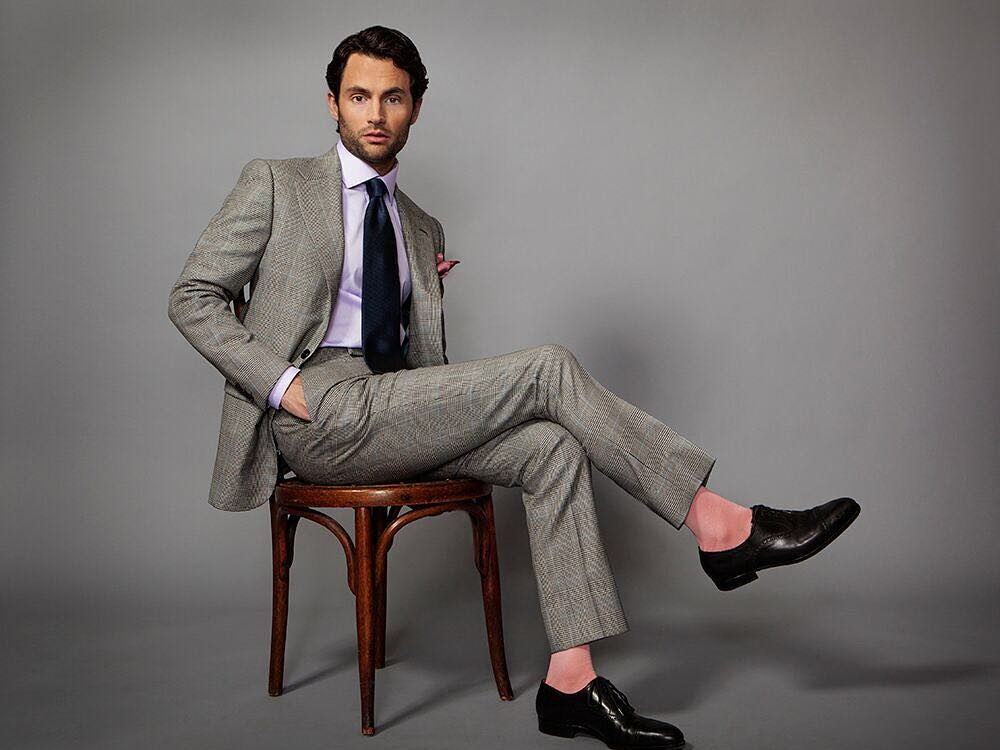 Penn Badgley sitting in a chair in a nice suit