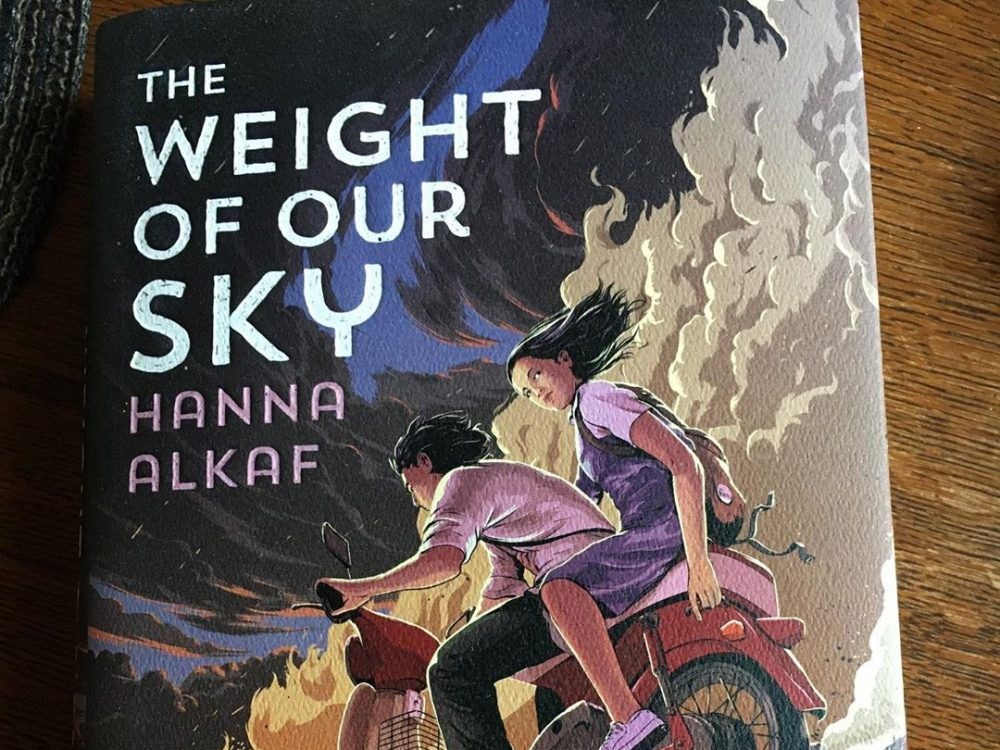 A copy of the YA novel The Weight of Our Sky