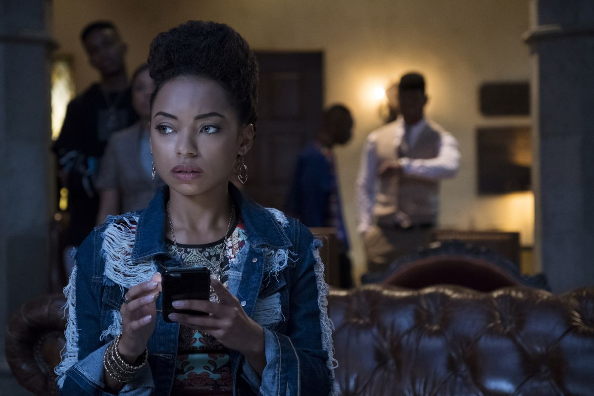 A main character from Dear White People checks her phone