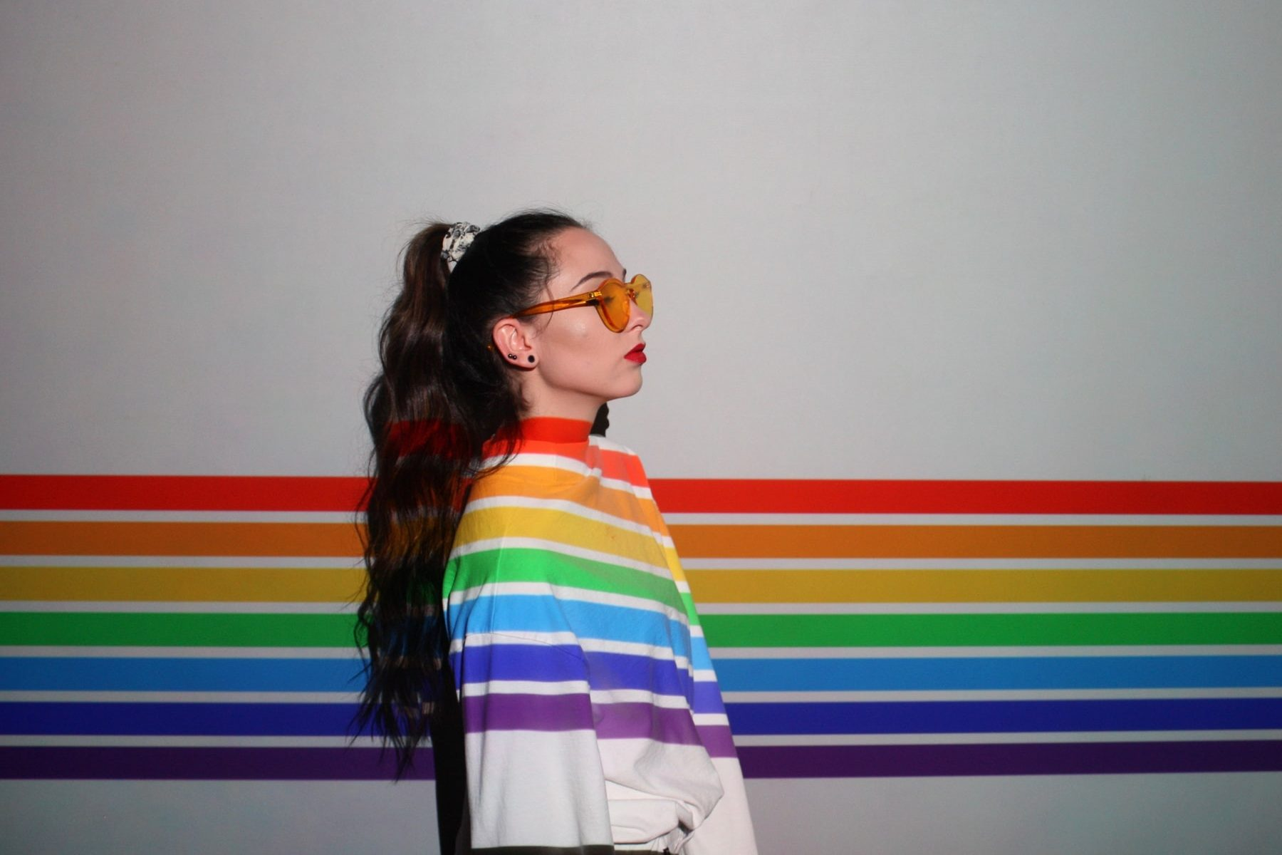 In an article about LGBTQ+ owned brands, a woman in a white shirt with rainbow stripes