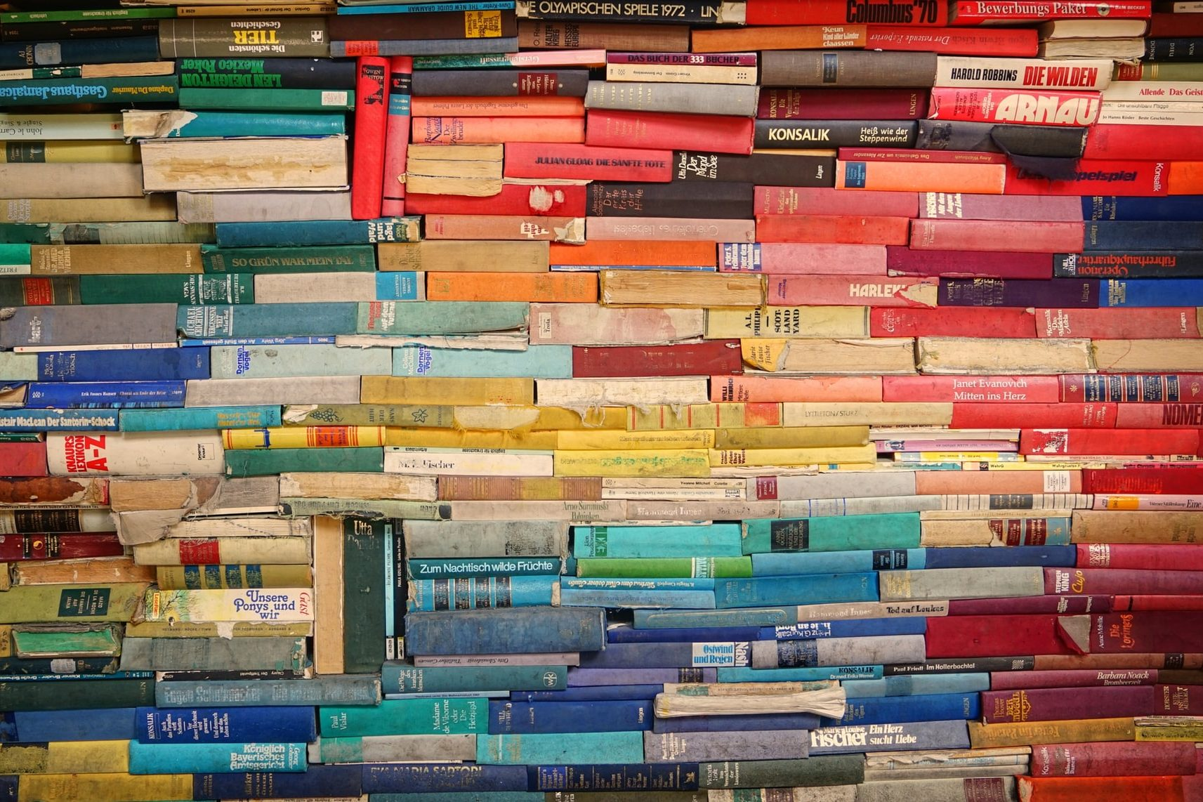 Writing for diversity: book spines arranged by color to resemble a rainbow.