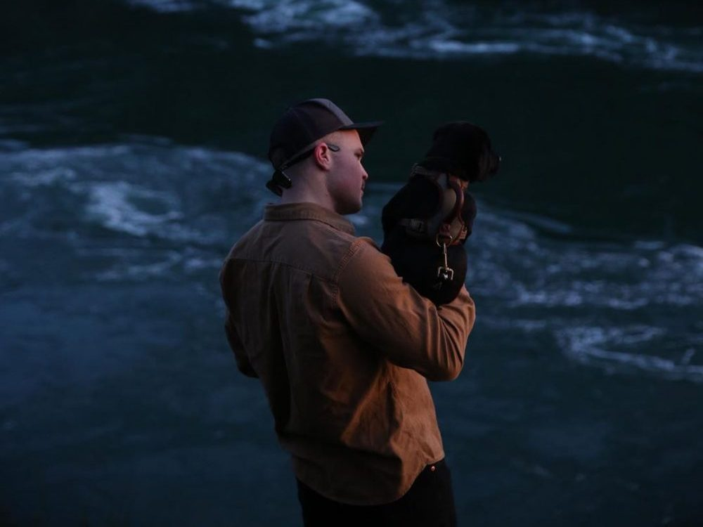 Country singer Zach Bryan stands in front of the ocean holding a dog