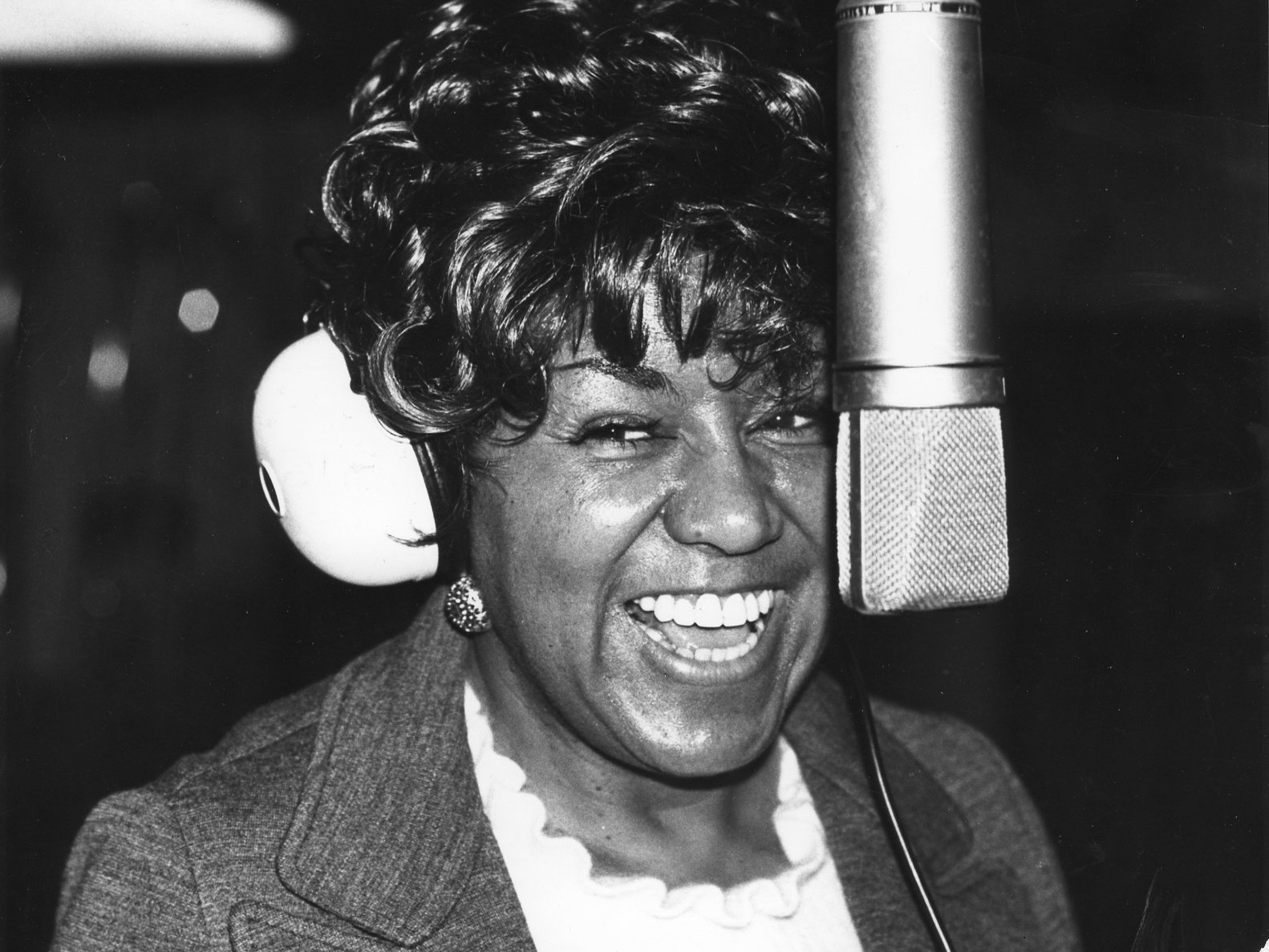 Image of POC songwriter Rose Marie McCoy smiling behind a microphone