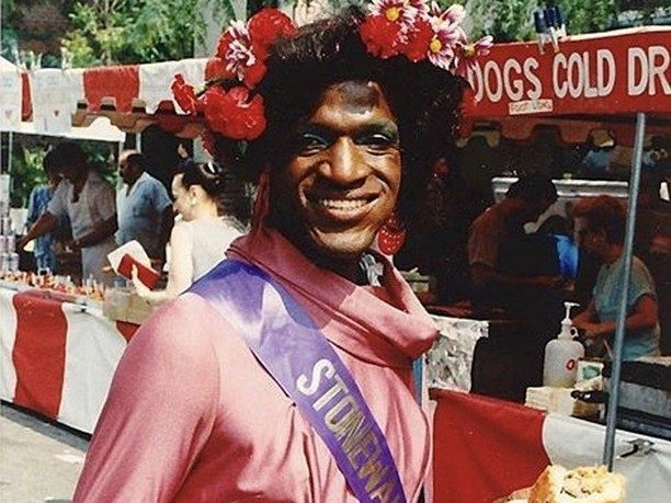 "Marsha P. Johnson posing with flowers in her hair and a sash that reads ""Stonewall""; black women activists"