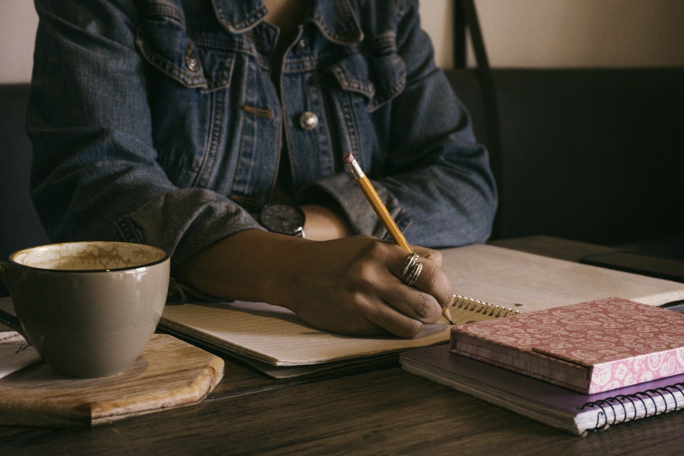 Image of person writing in a notebook on a table, in article about authors building a fan base