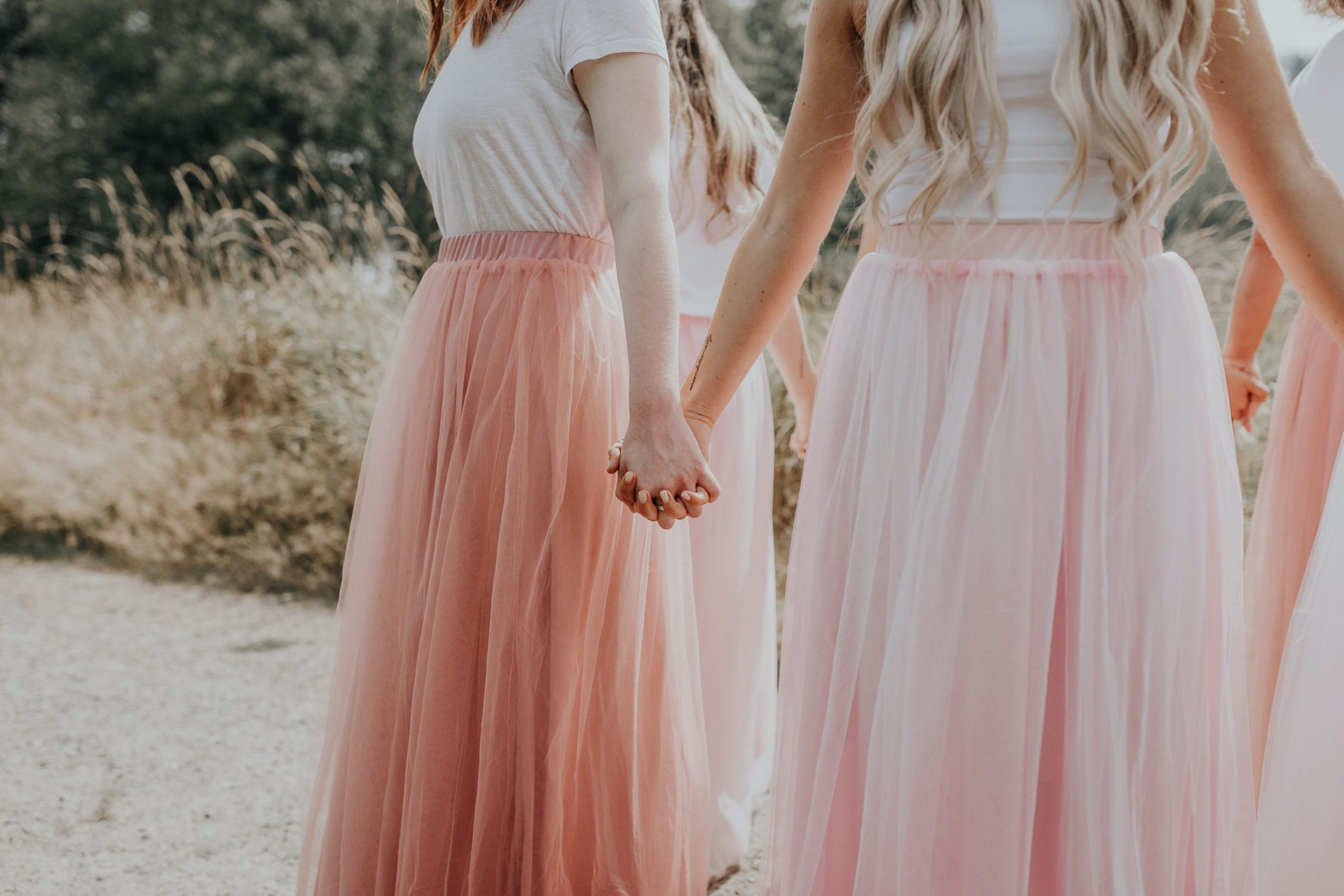women in pink skirts holding hands; toxic femininity