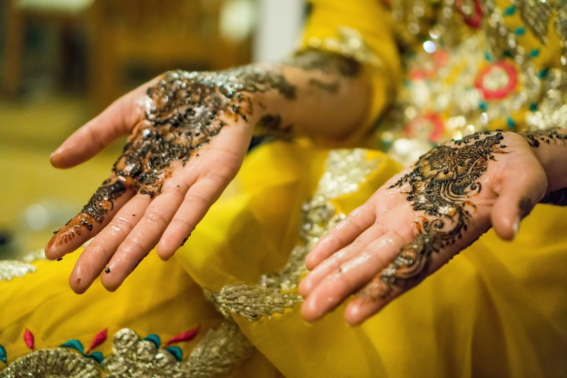 In article about Muslim clothing, woman's hands covered in henna and glitter