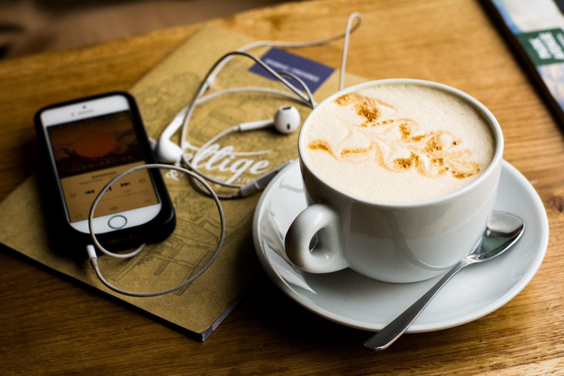 In an article about book review podcasts, a cup of coffee next to a phone with a podcast playing