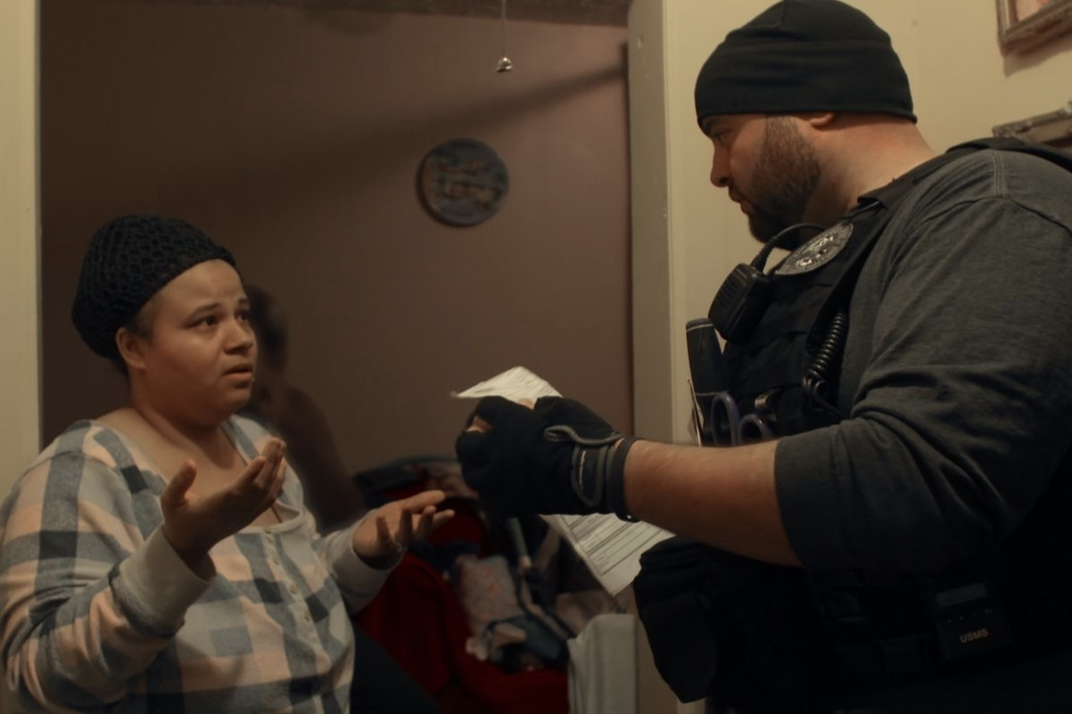 Image of a woman and a government agent in the docuseries Immigration Nation