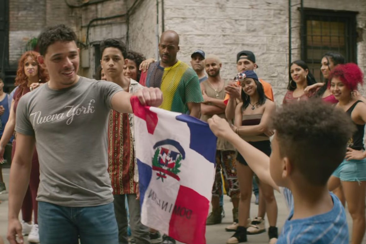 "A Latino man and boy hold a flag together in ""In the Heights."""