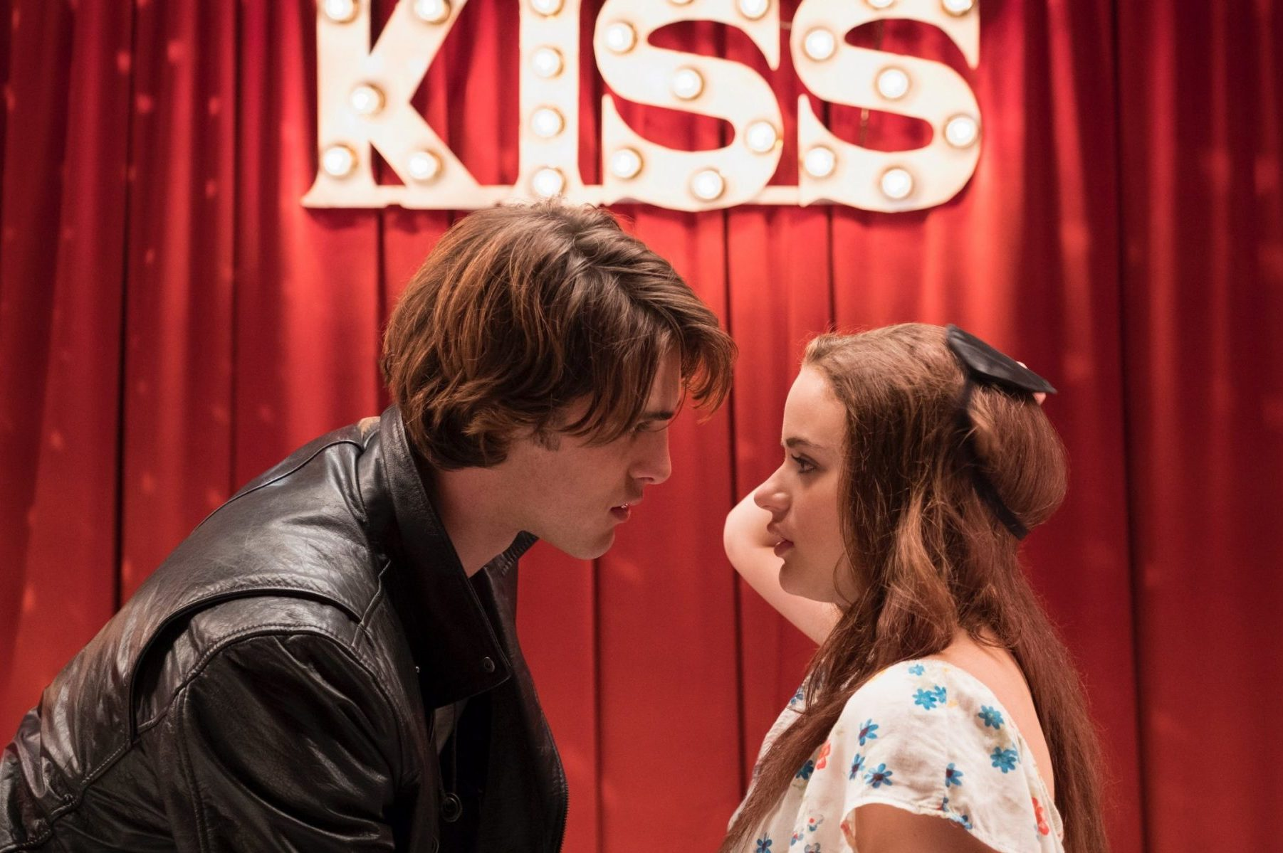 The two main characters prepare to kiss in the kissing booth.