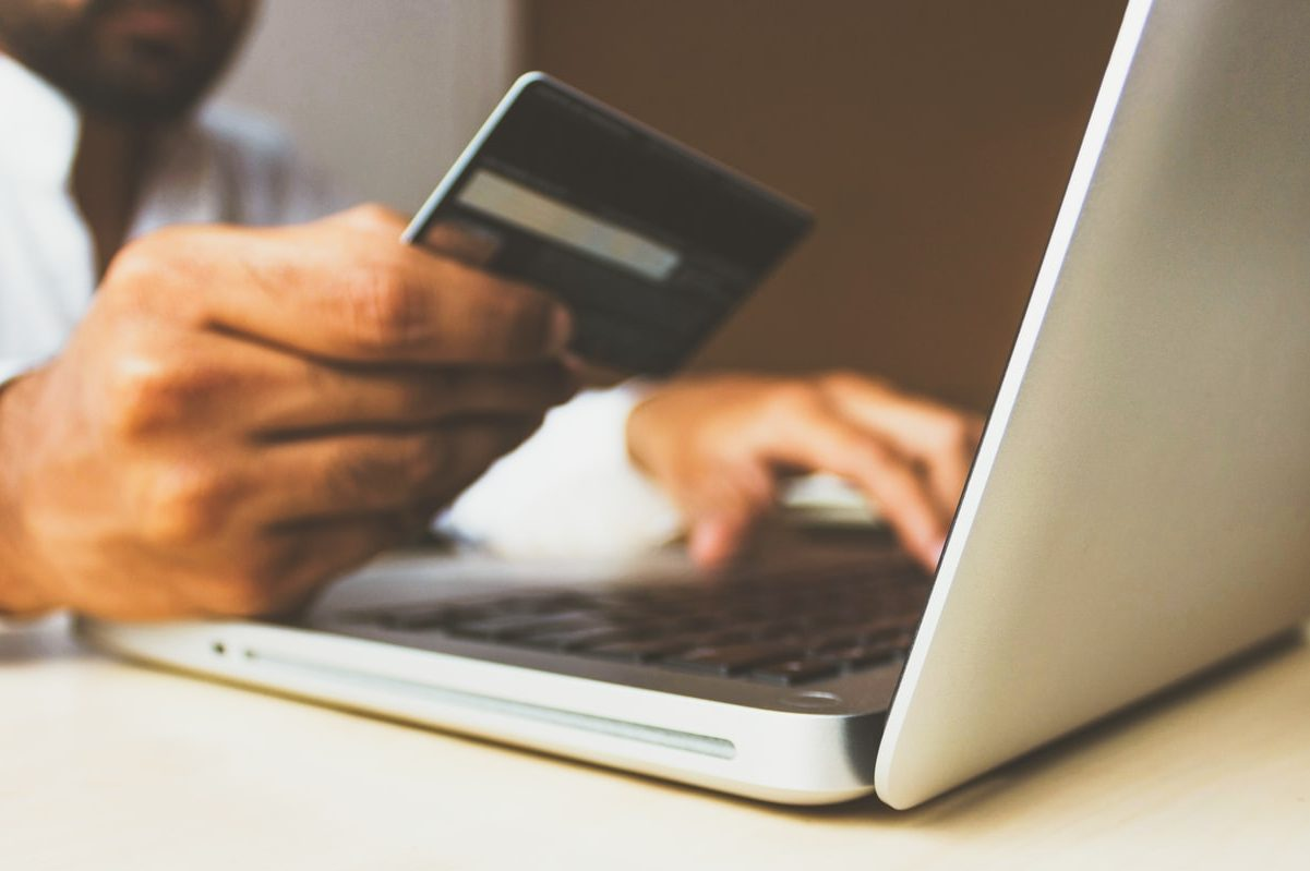 Image of a person at a laptop with a credit card in hand, in an article about using apps for informed shopping
