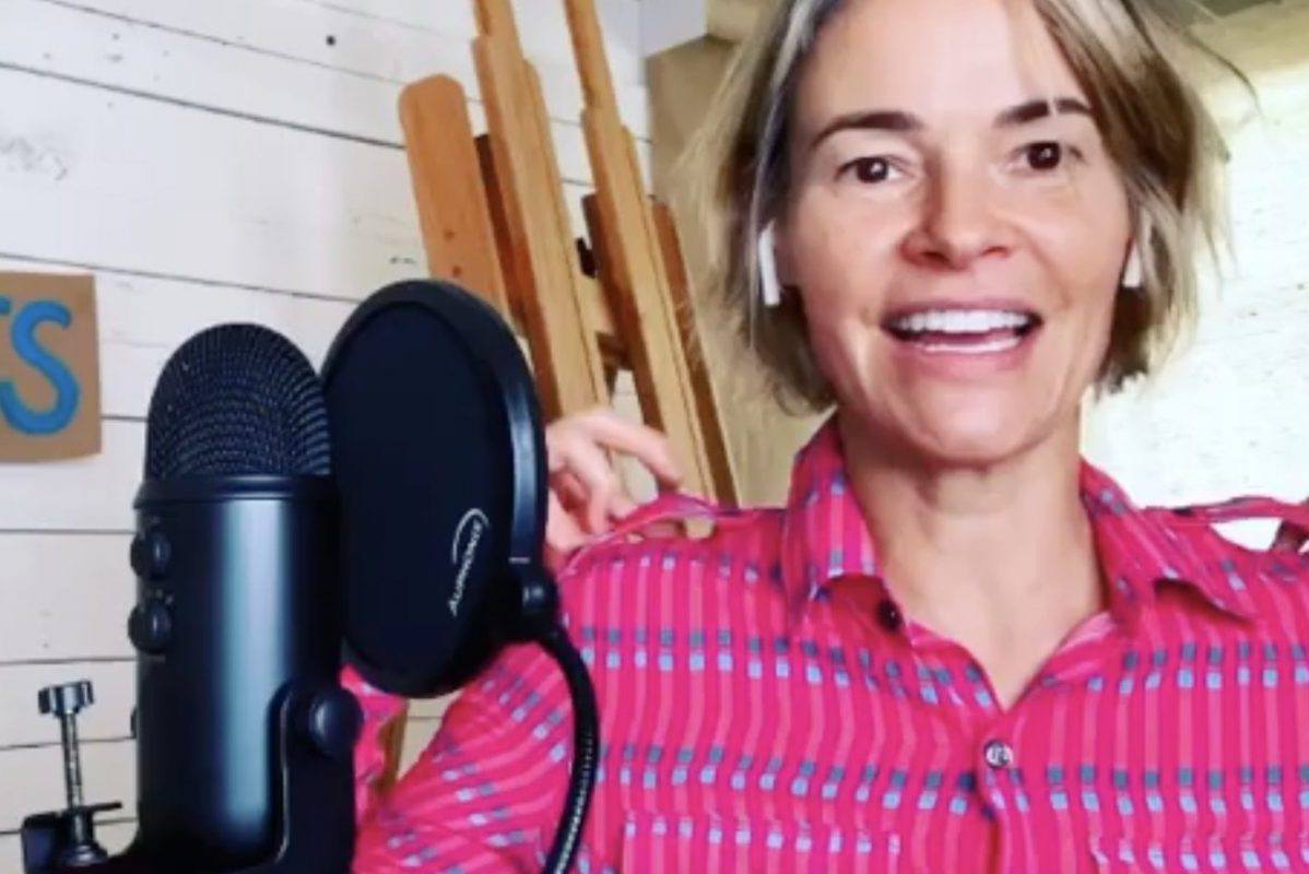 "Leisha Hailey talking into a microphone on the ""Pants"" podcast"