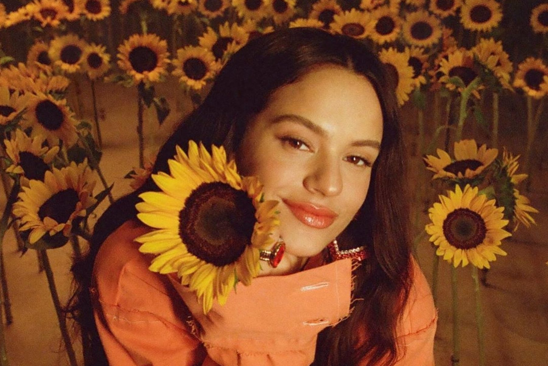 image of artist, Rosalía, among sunflowers