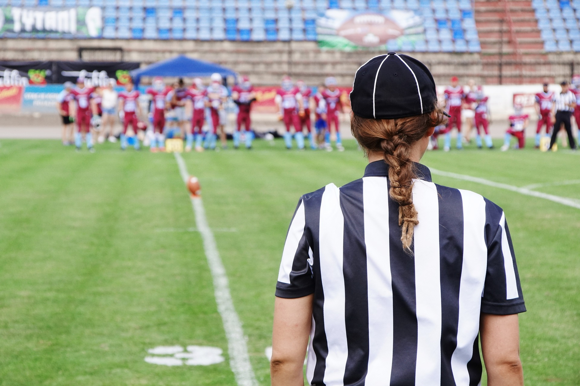 A coach stands on the football field observing her team.