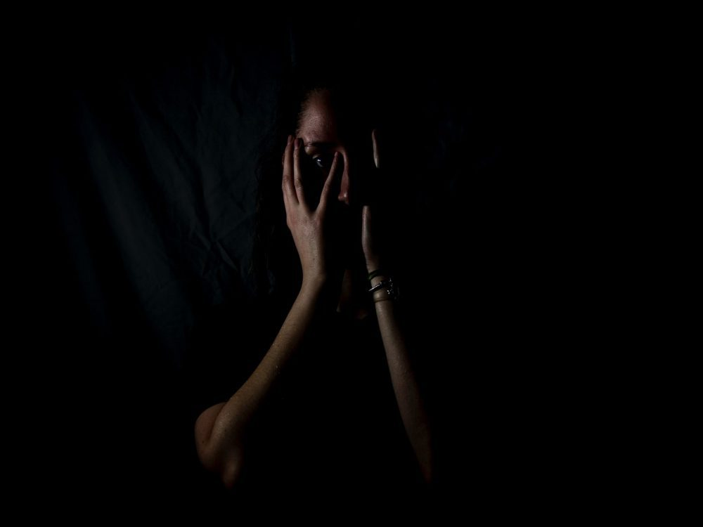 Image of a woman shrouded in darkness covering her face, in an article about imposter syndrome.