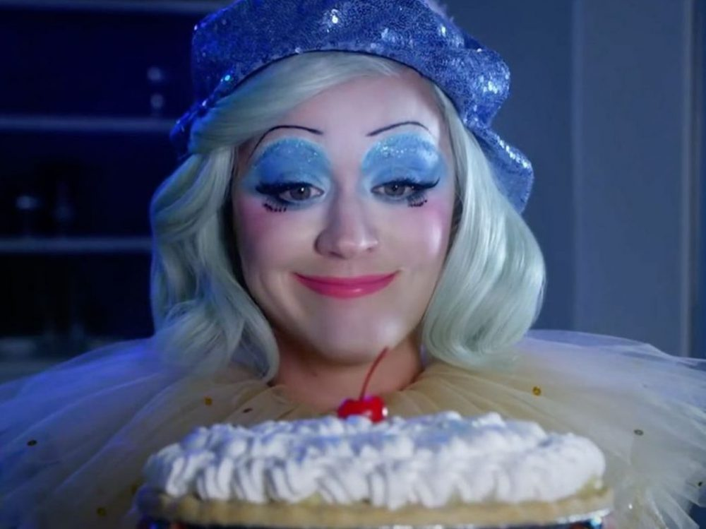 Katy Perry dressed as clown holding up a pie in the music video to her new album titled 'Smile'