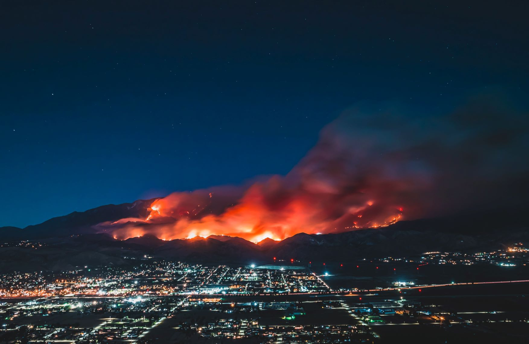 In an article about West Coast wildfires. The image is of a fire behind a California town.
