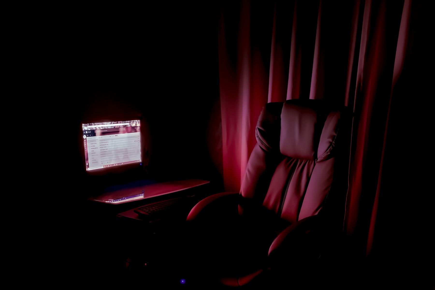 In article about text-based role-playing, a chair and a lit computer screen in a dark room