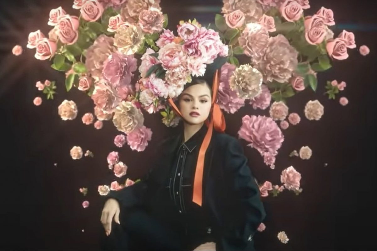 Image of Selena Gomez for her new ep Revelación, wearing a black suit with flowers behind her