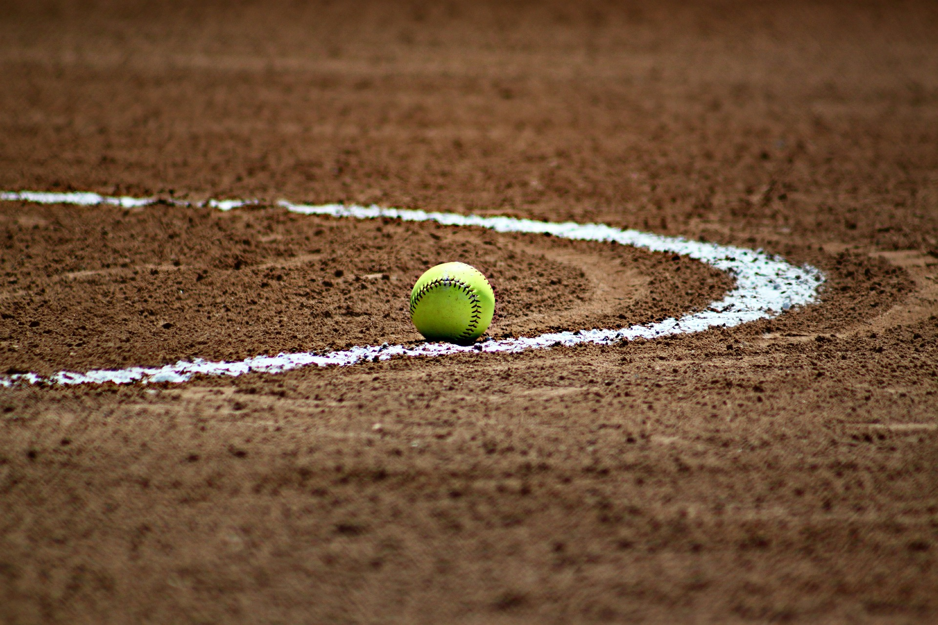 In an article about sports, a photo of a softball on a dirt field