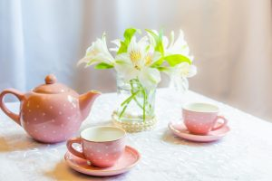A tea party set and white lilies in a vase on a white tablecloth.