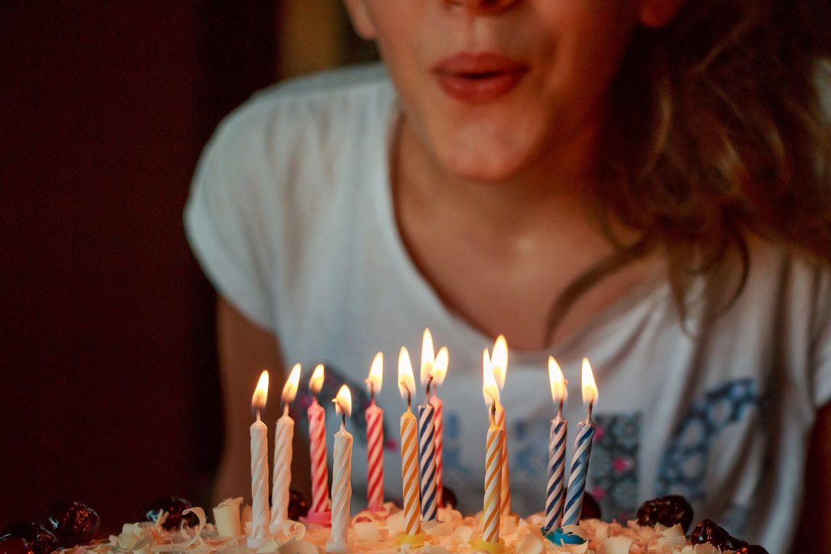 A woman blowing out birthday cake candles, for an article about birthday freebies.