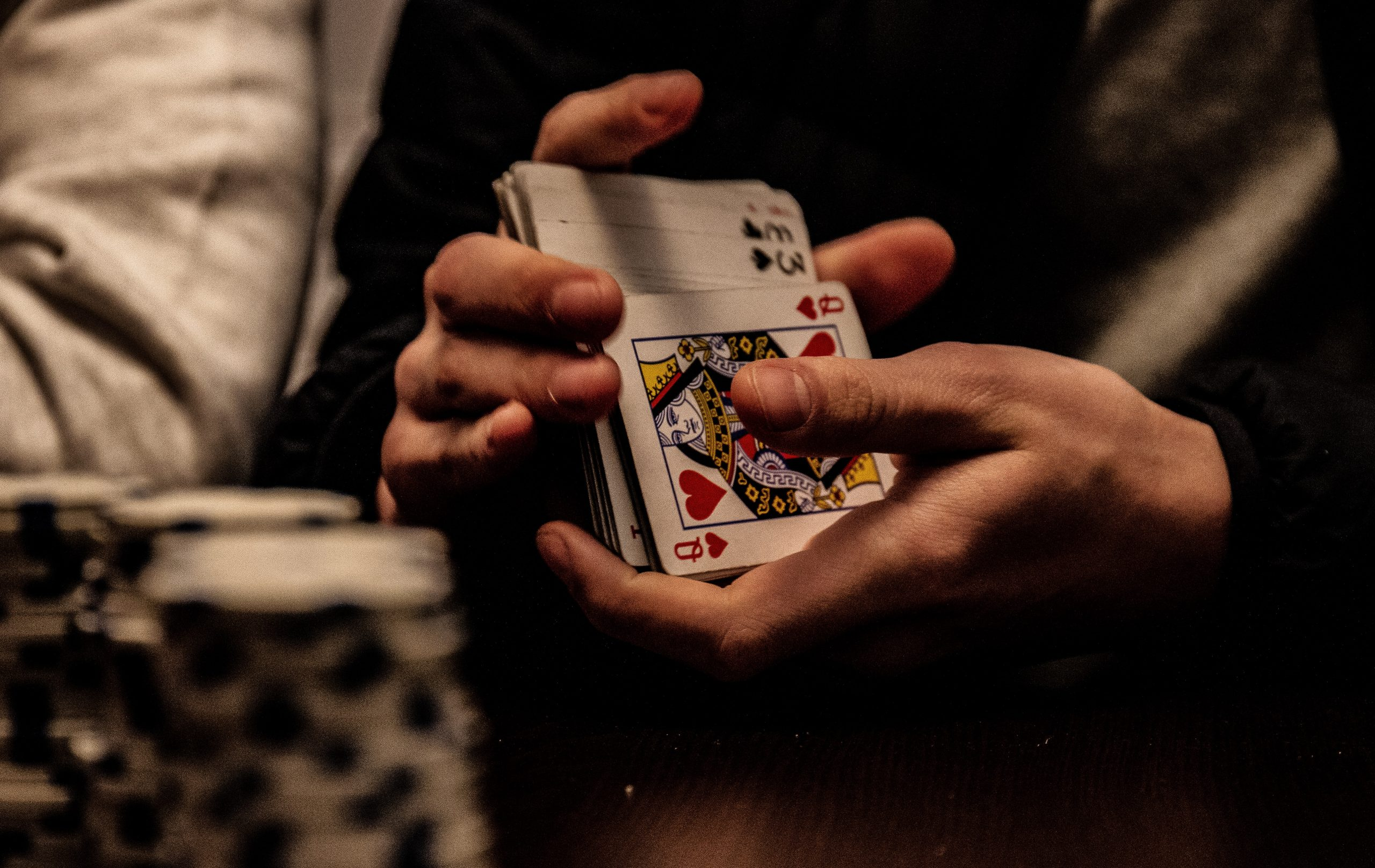 in an article about gambling, someone shuffling playing cards
