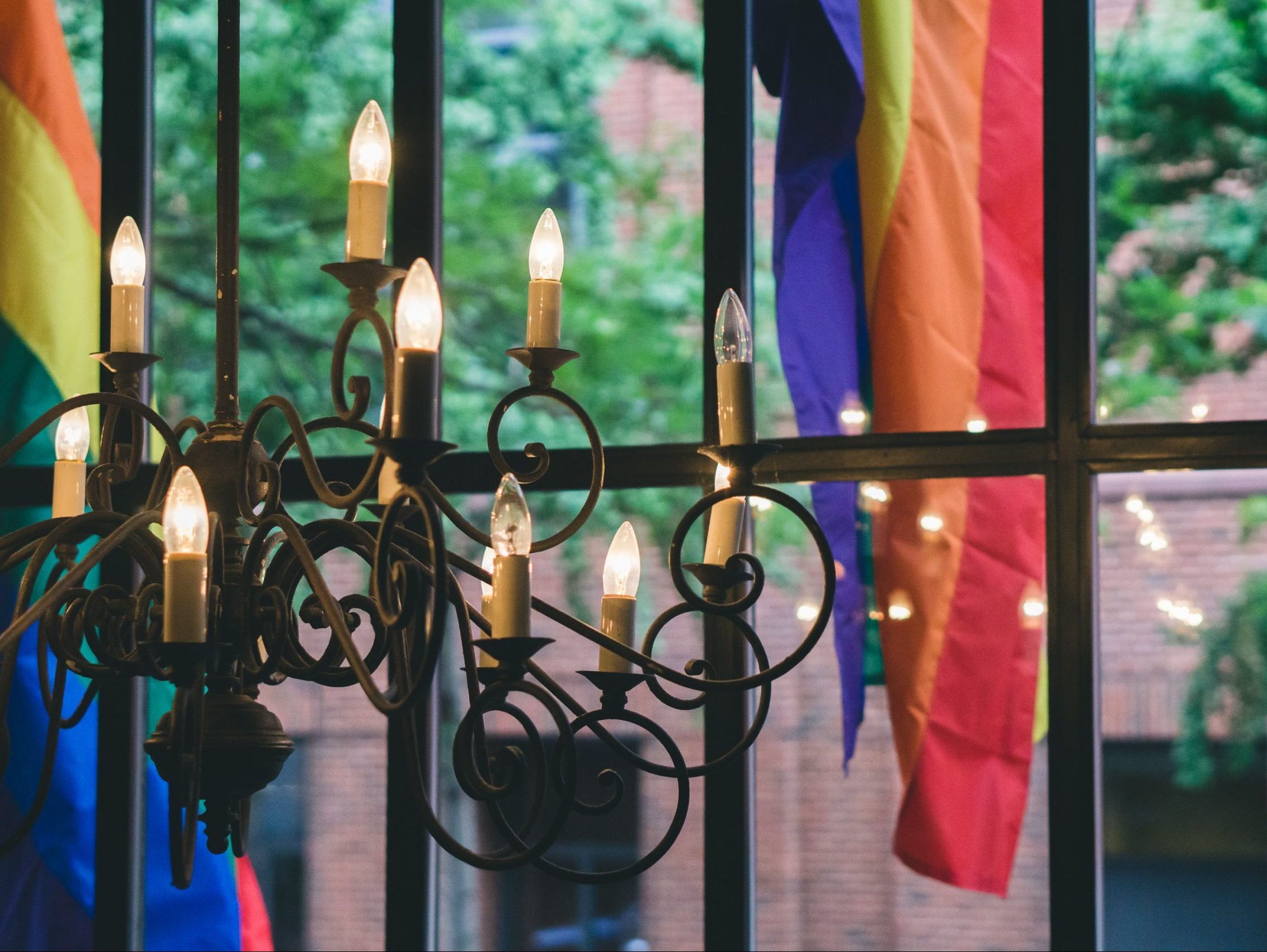 In an article about lesbian bars, a chandelier in front of a window looking out to pride flags